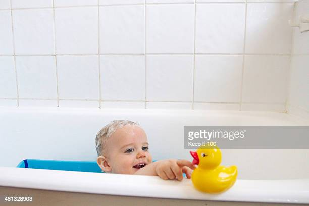Baby in the bath reaching for rubber duck