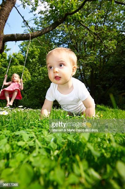 Baby in the garden, girl on the swing