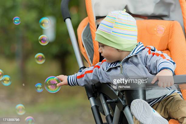 Baby in the stroller looking at foam balloons