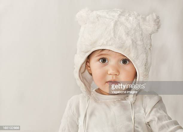 baby in white - fur hat stock photos and pictures