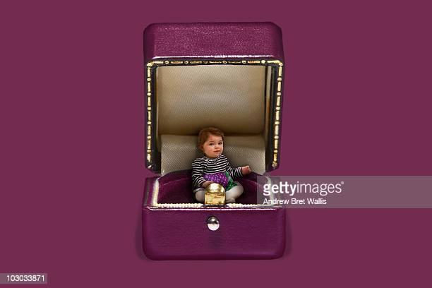 baby inside an open pink jewellery box