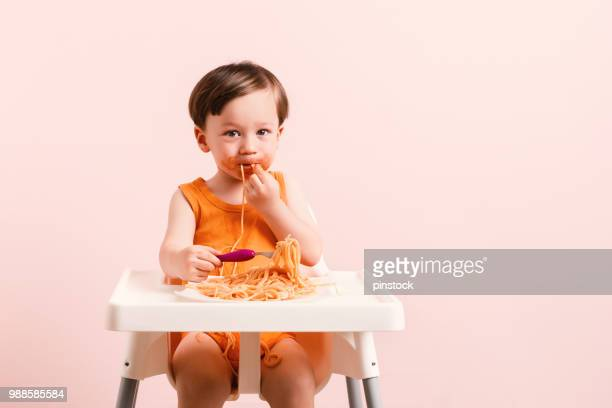 Baby is eating spaghetti.