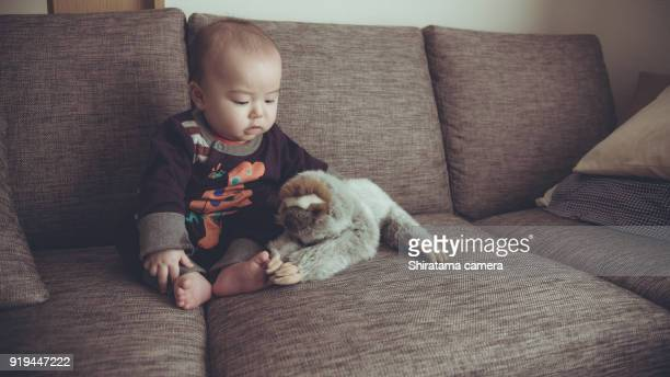 Baby is playing with a stuffed animal