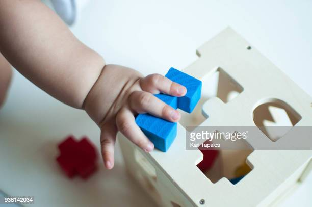 A baby is playing with a wooden toy block