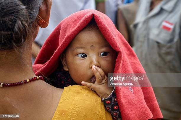 A baby is seen as her mother waits to take tent and food supplies at Charuwa village 52 Kilometer east from Kathmandu on May 11 2015 The number of...