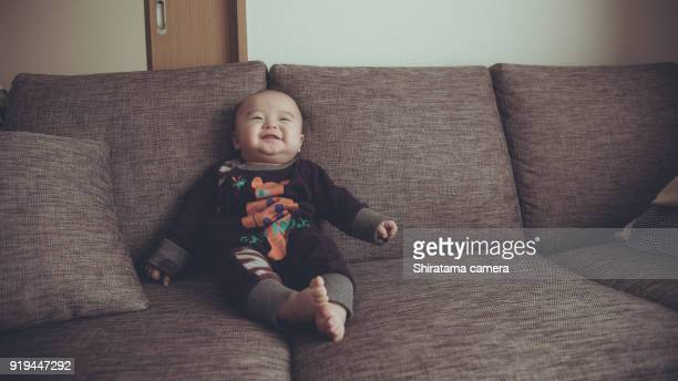 baby is sitting on the sofa