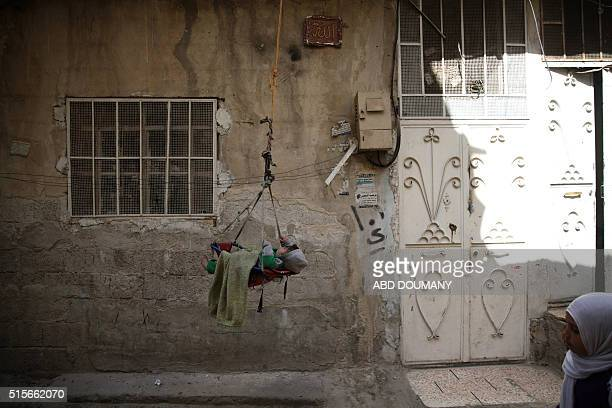 A baby is suspended on a swingingrope outside a house in the rebelheld suburb of Tishreen on the outskirts of the Syrian capital Damascus on March 14...