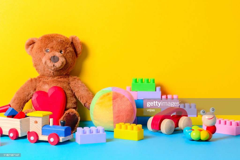 Baby kid toys collection on blue and yellow background : Stock Photo