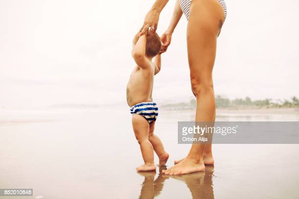 Baby learning to walk on sandy beach