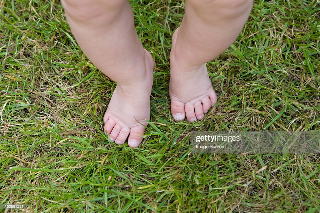 Baby legs and feet on grass : Stock Photo