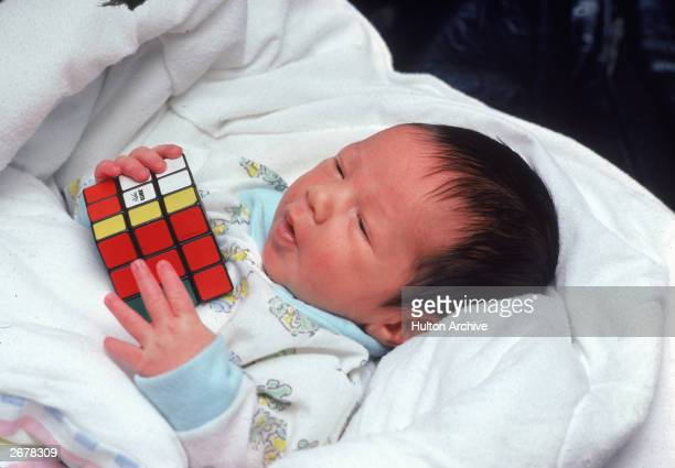 A baby lies in bed holding a Rubik's Cube circa 1981