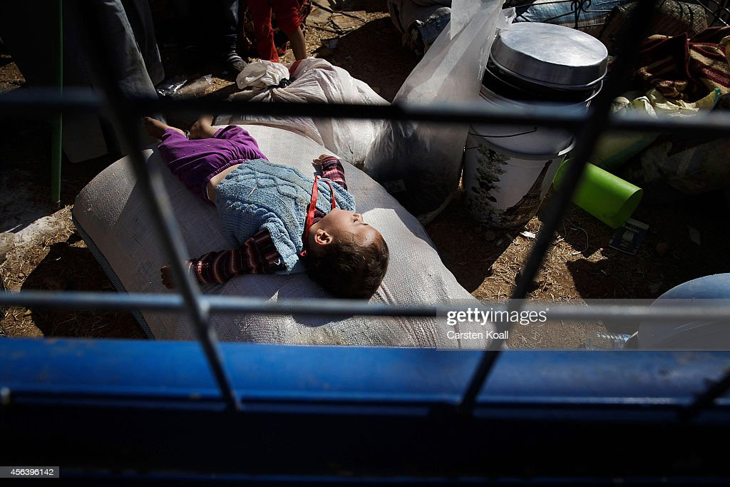 A baby lies on a sack as refugees wait behind a fence before crossing the border from Syria into Turkey September 30, 2014 near Suruc, Turkey. Kurdish troops are engaged in a battle against fighters of the Islamic State (IS, also called ISIS and ISIL) to defend the strategic nearby Kurdish border town of Kobani (also called Ayn Al-Arab), which ISIS has surrounded on three sides. The Turkish Parliament is due to vote on a measure on October 2, which would allow Turkish ground forces to enter Syria, creating a buffer zone to protect fleeing refugees from the ISIS advance.