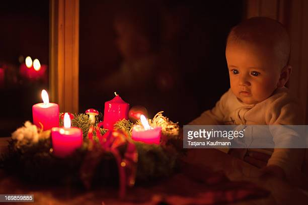 Baby looking at advent wreath with candles
