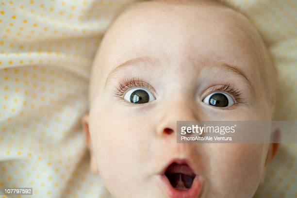 baby looking at camera with surprised expression, portrait - サプライズ ストックフォトと画像