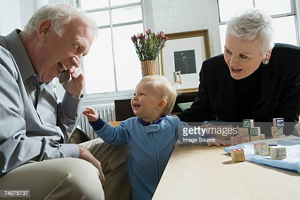 Baby looking at grandfather with cellphone