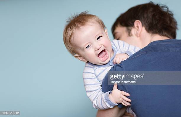 Baby looking over Daddy's Shoulder, laughing