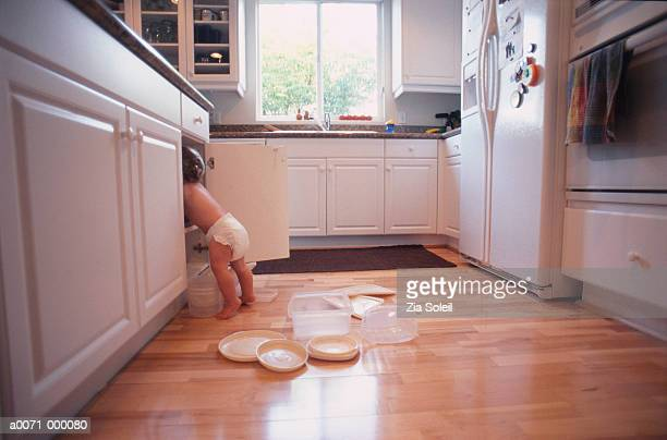baby looks in kitchen cupboard - naughty america foto e immagini stock