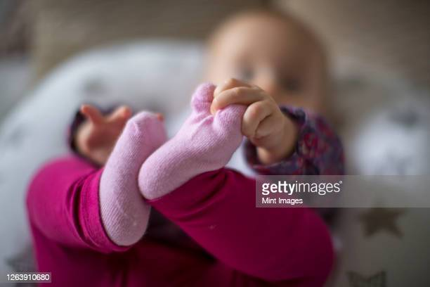 baby lying back holding its foot - pink colour stock pictures, royalty-free photos & images