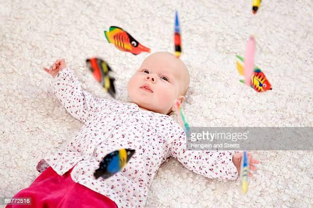 baby lying beneath mobile toy