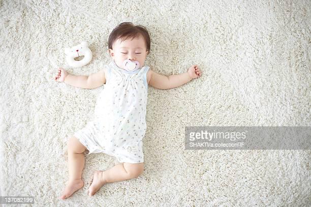 Baby lying down on carpet sleeping