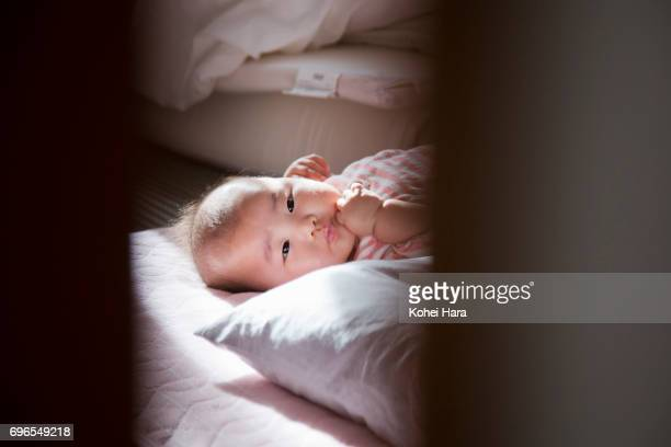 Baby lying down on the bed and looking into camera through the door.