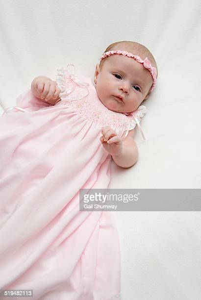 Baby lying down wearing a pink dress