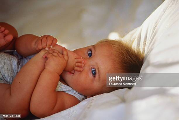 Baby (6-8 months) lying on bed, sucking big toe