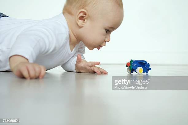 Baby lying on floor, looking at toy airplane