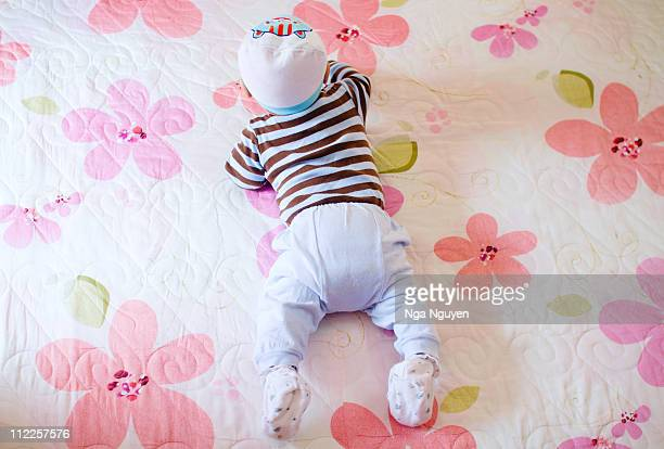 baby lying on flowery bedspread - nga nguyen stock pictures, royalty-free photos & images