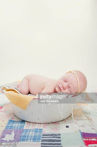 Baby lying on front in bowl