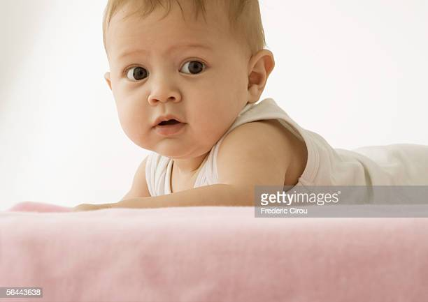 Baby lying on stomach, holding head up