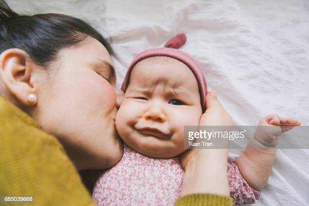 baby making funny face when mother kiss - candid stock pictures, royalty-free photos & images