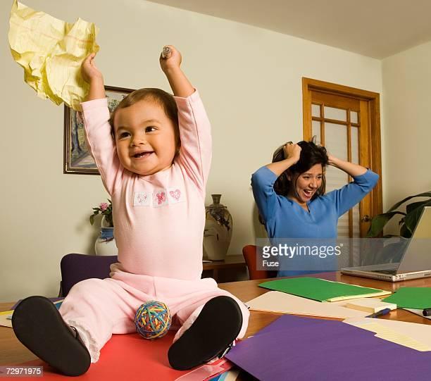 Baby making mischief on mother's desk