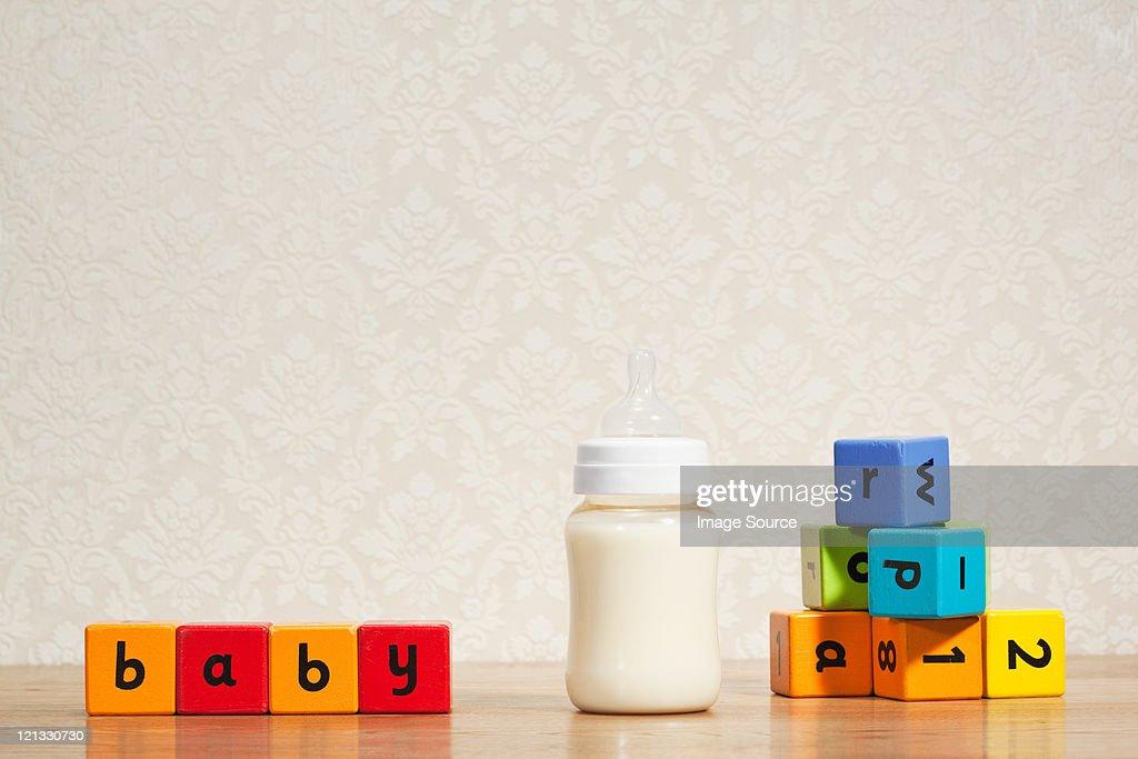 Baby milk and alphabet blocks : Stock Photo