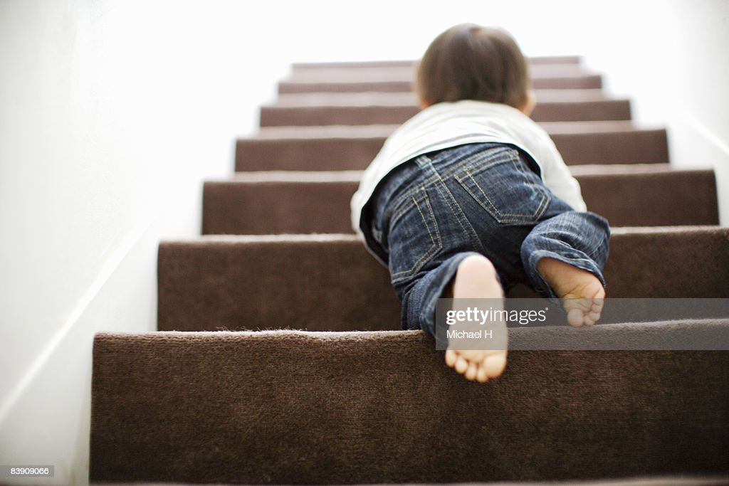 Baby mounts the stairs by crawling : Stock Photo