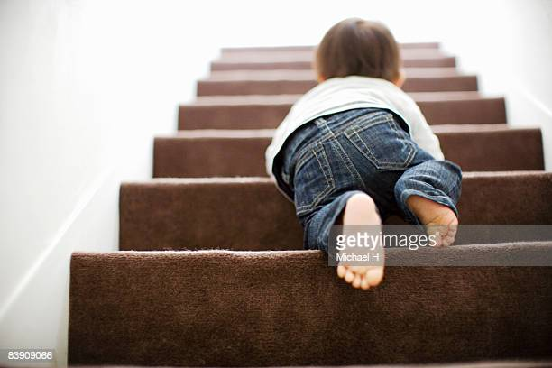 baby mounts the stairs by crawling - steps stock photos and pictures