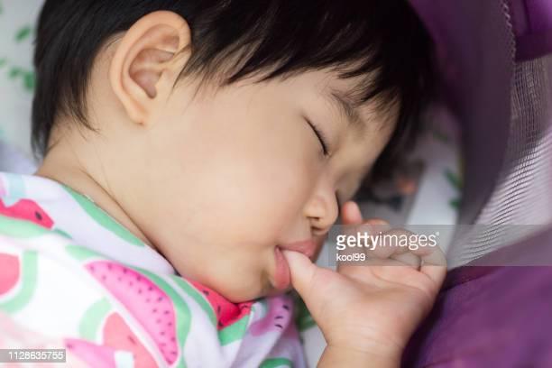 bebê dormindo e chupar o dedo - chupando dedo - fotografias e filmes do acervo