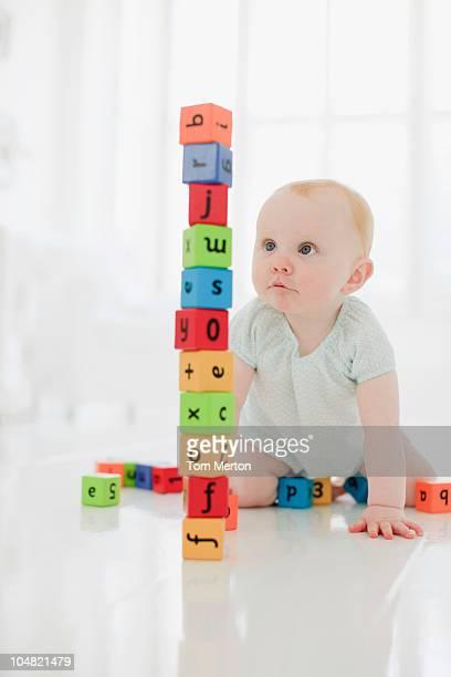 Baby on floor looking at stacked wood blocks