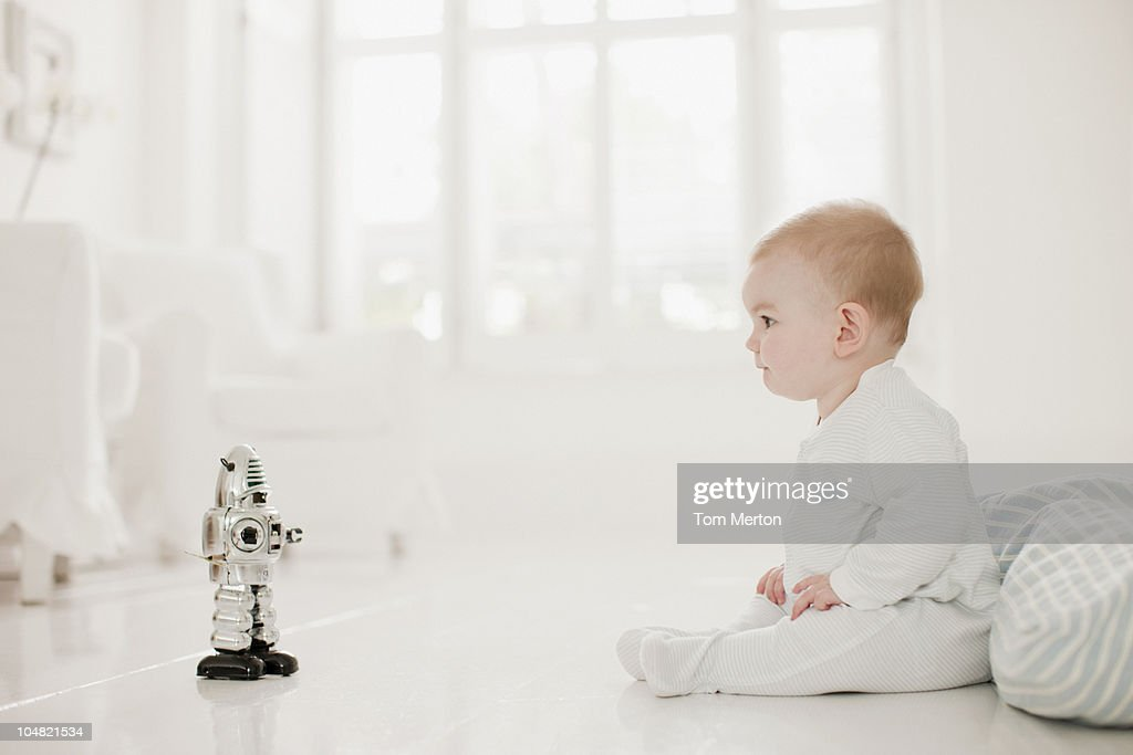 Baby on floor looking at toy robot : Stock Photo
