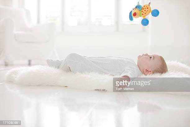 Baby on rug  for hanging toy overhead