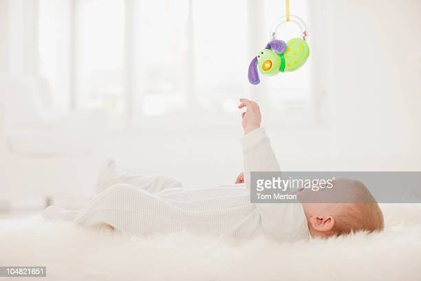 Baby on rug reaching for hanging toy overhead