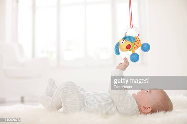 baby on rug reaching for hanging toy overhead - toy stock pictures, royalty-free photos & images