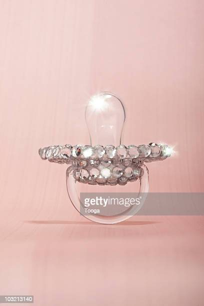 Baby pacifier covered in diamonds on pink
