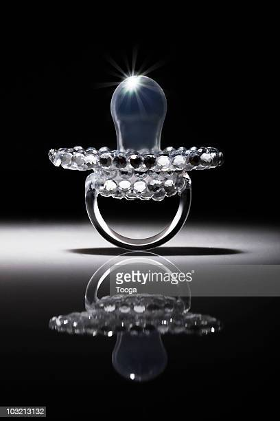 Baby pacifier covered in diamonds with spotlight