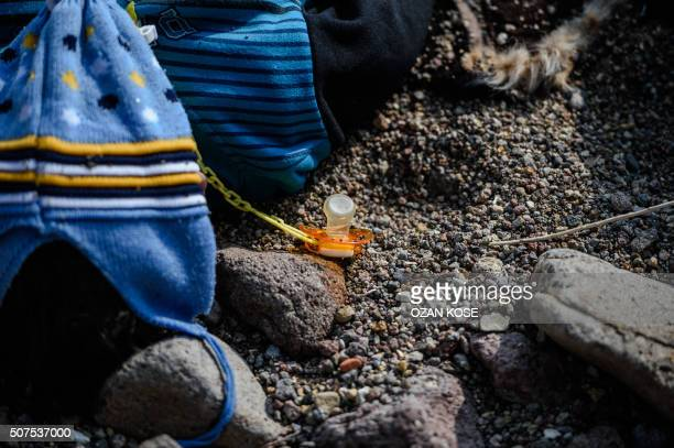 A baby pacifier lies next to the body of a child on a beach in Canakkale's Bademli district on January 30 2016 after at least 33 migrants drowned...