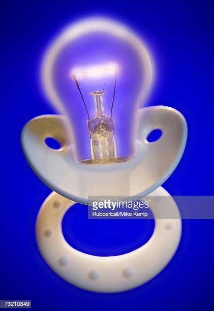 Baby pacifier with lightbulb abstract concept