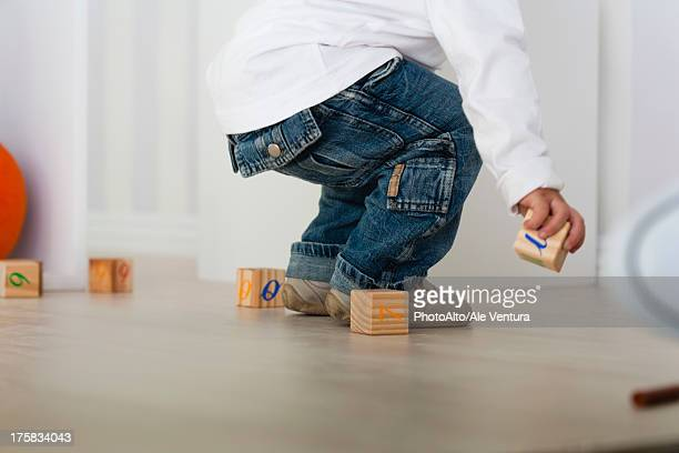 Baby picking up block from floor, low section