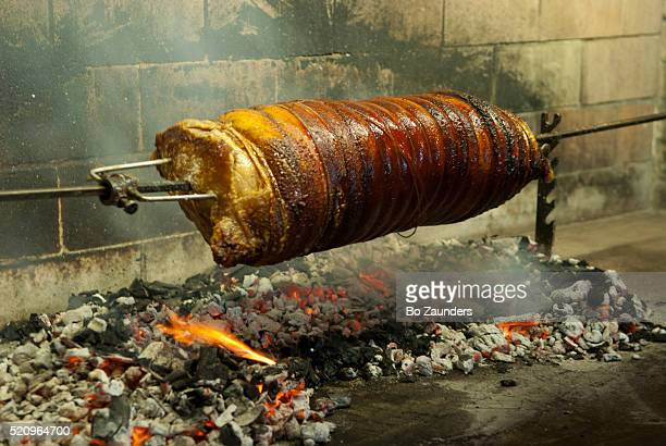 Baby pig roasting on a spit over a coal fire