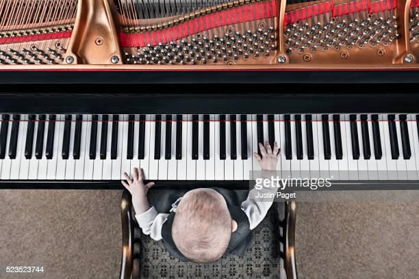 baby (6-12 months) playing baby grand piano - wonderkind stockfoto's en -beelden