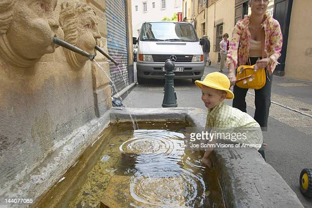 Baby playing in Fountain d'Espeluque of 1618 located in Place Martyrs de la Resistance Aix en Provence France